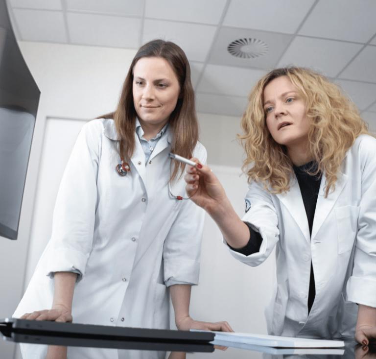Lekarki analizują obraz na monitorze.