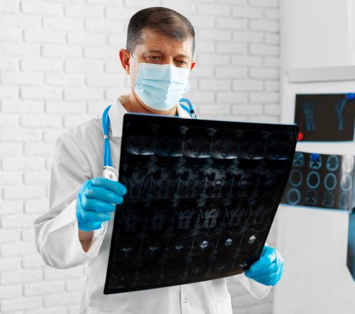 Doświadczony lekarz w maseczce analizuje obraz mri